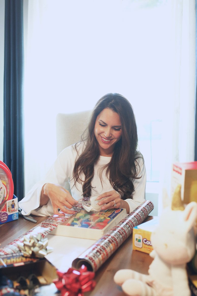 Brunette woman wrapping a Christmas gift | The ultimate toddler christmas gift life | Lifewithmar.com